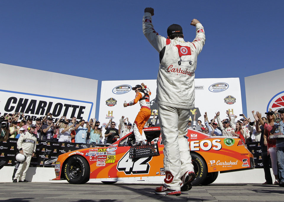Photo - Kyle Larson celebrates in Victory Lane after winning the NASCAR Nationwide series History 300 auto race at Charlotte Motor Speedway in Concord, N.C., Saturday, May 24, 2014. (AP Photo/Chuck Burton)