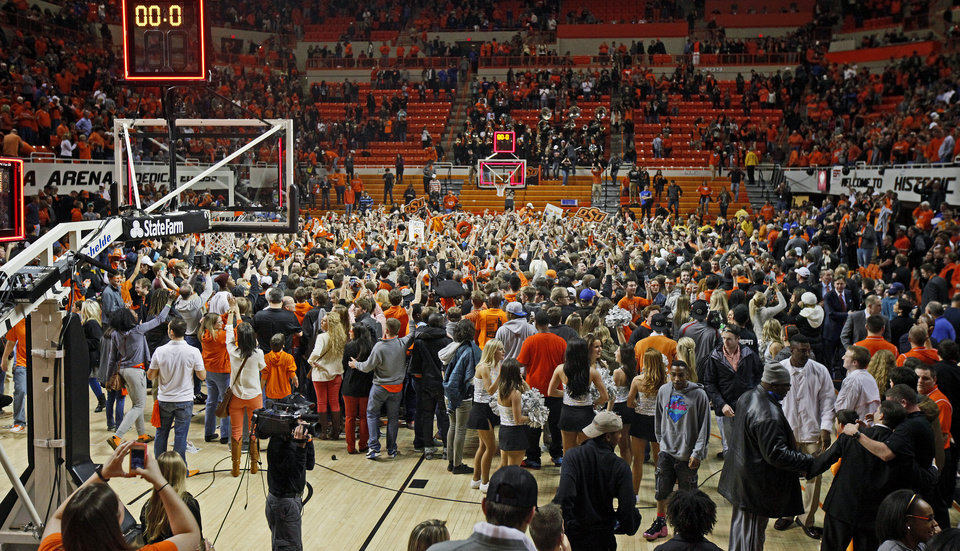 Photo - Oklahoma State fans rush the court after  an NCAA college basketball game between Oklahoma State University (OSU) and the University of Kansas at Gallagher-Iba Arena in Stillwater, Okla., Saturday, March 1, 2014. Oklahoma State won 72-65. Photo by Bryan Terry, The Oklahoman