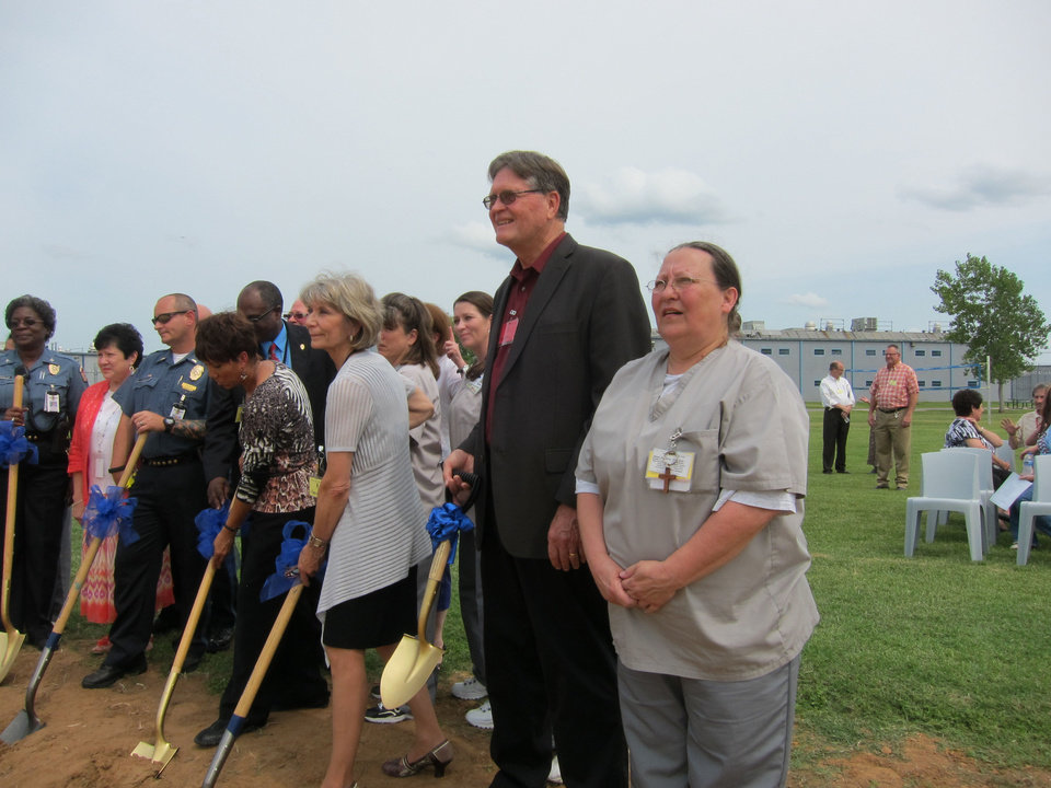 Photo - The Rev. Joe Wilson, domestic coordinator for World Mission Builders, and inmate Mary Marney of Tulsa stand with other inmates and faith community volunteers participating in a recent groundbreaking for a chapel at Mabel Bassett Correctional Center in McLoud.  Carla Hinton - The Oklahoman