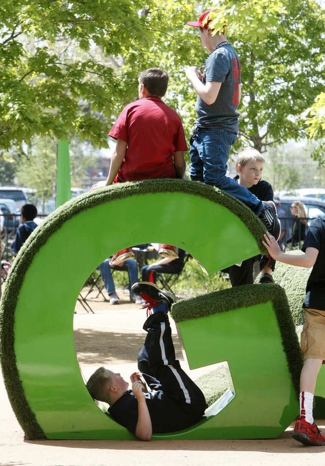 At right: Children play on a letter sculpture in the kids� area Thursday during the Festival of the Arts in downtown Oklahoma City.