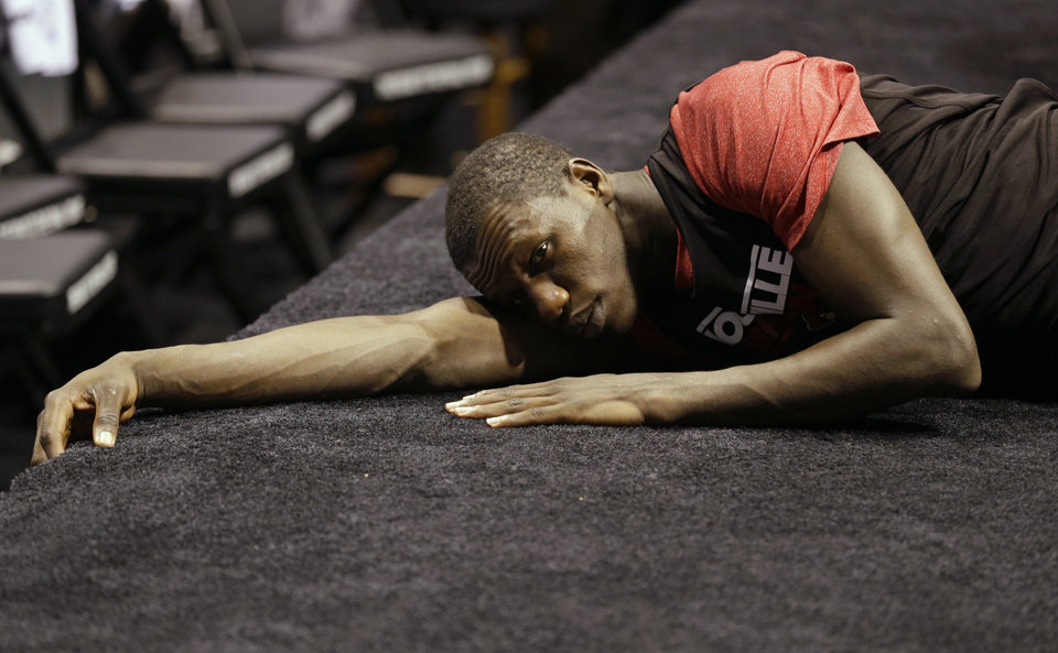 Photo - Louisville center Gorgui Dieng stretches on the floor during practice for a regional semifinal game in the NCAA college basketball tournament, Thursday, March 28, 2013, in Indianapolis. Louisville plays Oregon on Friday. (AP Photo/Michael Conroy)  Michael Conroy