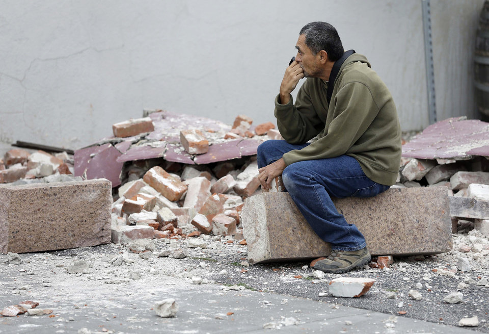 Photo - Ron Peralez, of Vacaville, Calif., sits on rubble and looks at earthquake-damaged buildings Monday, Aug. 25, 2014, in Napa, Calif. The San Francisco Bay Area's strongest earthquake in 25 years struck the heart of California's wine country early Sunday, igniting gas-fed fires, damaging some of the region's famed wineries and historic buildings, and sending dozens of people to hospitals. (AP Photo/Eric Risberg)