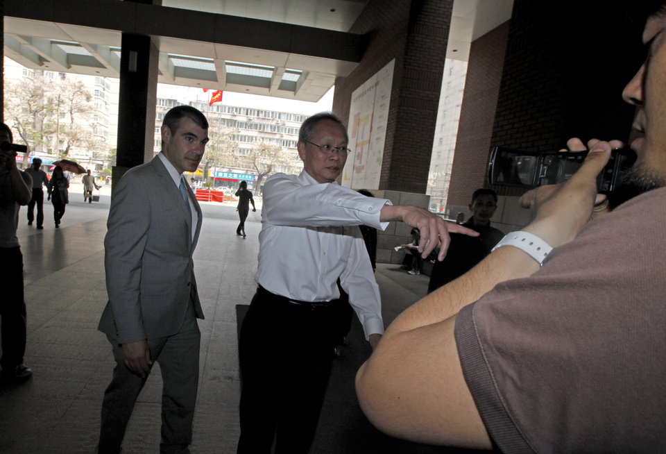 Photo -   Robert S. Wang, center, deputy chief of mission at the U.S. embassy in Beijing, gestures as he walks with an unidentified U.S. embassy staff, left, outside the hospital where blind activist lawyer Chen Guangcheng is recuperating in Beijing Friday, May 4, 2012. The Chinese activist at the center of a diplomatic standoff between the United States and China said Friday his situation is