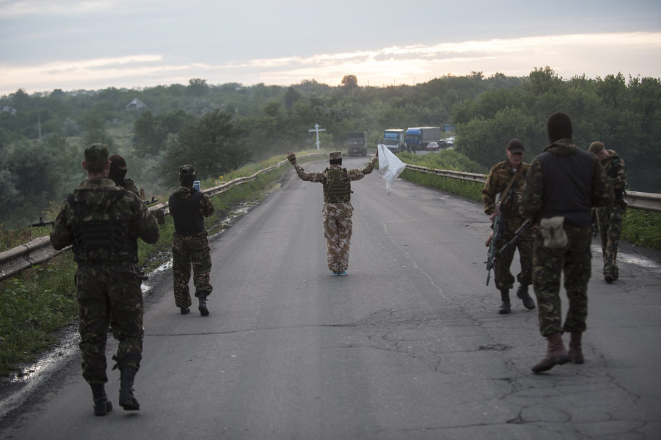 Photo - Pro-Russian fighters wave a white flag to start a handover of the bodies of Ukrainian troops killed in a plane shot down near Luhansk, at a check point in the village of Karlivka near Donetsk, eastern Ukraine, Wednesday, June 18, 2014. The two sides managed to arrange a brief truce Wednesday evening in the eastern town of Karlivka to allow pro-Russian forces to hand over the bodies of 49 Ukrainian troops who died when the separatists shot down a transport plane bound for the airport in Luhansk last weekend.  (AP Photo/Evgeniy Maloletka)