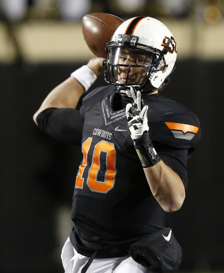 Photo - Oklahoma State quarterback Clint Chelf (10) passes against Baylor in the first quarter of an NCAA college football game in Stillwater, Okla., Saturday, Nov. 23, 2013. (AP Photo/Sue Ogrocki)