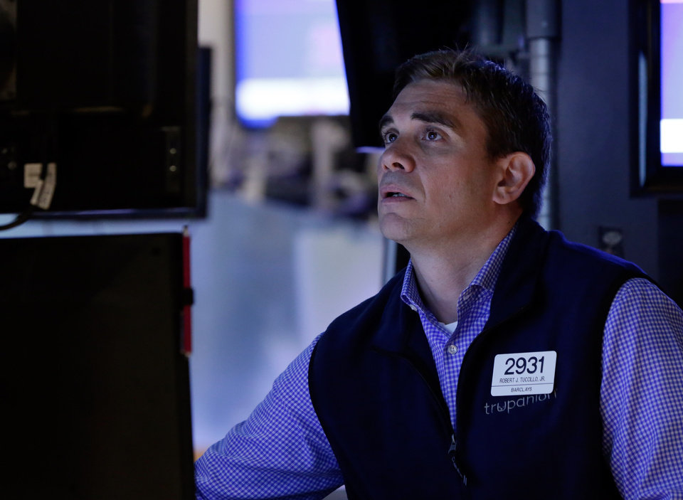 Photo - Specialist Robert Tuccillo studies his monitors as he works on the floor of the New York Stock Exchange Friday, July 18, 2014. U.S. stocks are opening higher after Google, Honeywell and other big companies report their quarterly results. (AP Photo/Richard Drew)