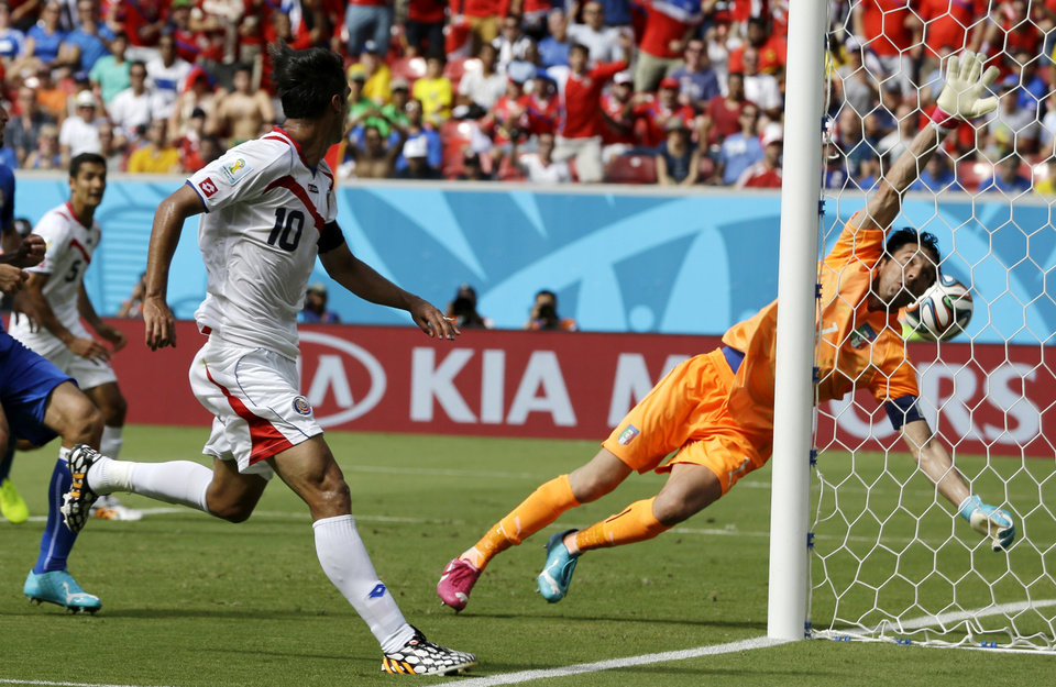 Photo - Costa Rica's Bryan Ruiz (10) watches as the ball goes past Italy's goalkeeper Gianluigi Buffon to score his side's first goal during the group D World Cup soccer match between Italy and Costa Rica at the Arena Pernambuco in Recife, Brazil, Friday, June 20, 2014.  (AP Photo/Ricardo Mazalan)