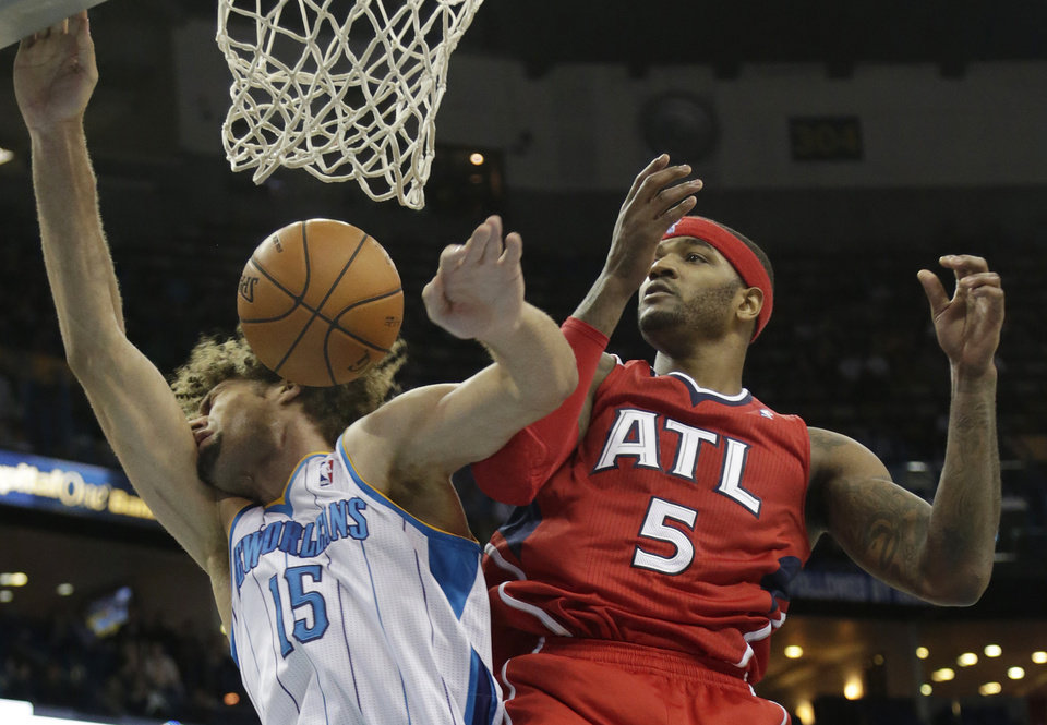 Photo - Atlanta Hawks small forward Josh Smith (5) fights for a rebound with New Orleans Hornets center Robin Lopez (15) during the fourth quarter of an NBA basketball game at the New Orleans Arena in New Orleans Tuesday, Jan. 1, 2013. Atlanta beat New Orleans 95-86. (AP Photo/Dave Martin)