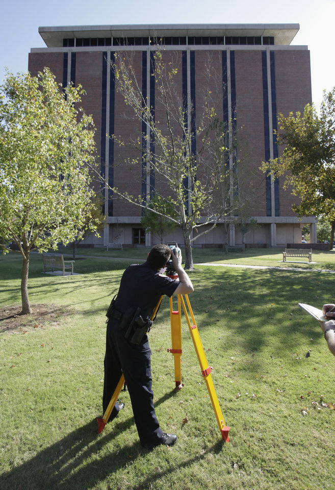 OU: University of Oklahoma police offficer Tony Navarro uses a laser device to check the effects of a reported 4.3 magnitude earthquake at Dale Hall Tower on the University of Oklahoma campus on Wednesday, October 13, 2010, in Norman, Okla.    Photo by Steve Sisney, The Oklahoman. ORG XMIT: KOD