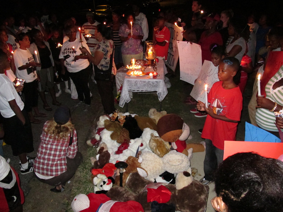 Friends and relatives of 15-year-old shooting victim Justin Thompson gather around a pile of stuffed animals during a candlelight vigil on Sept. 28, 2012 in Memphis, Tenn. The teen's shooting by an off-duty Memphis police officer is the latest incident being used by critics of the city's police department to push for reforms from the outside. This year, at least 23 Memphis officers and civilian personnel have been charged with crimes, from DUI and drug dealing to human sex trafficking. Going back to 2004, dozens of officers in Tennessee's largest city have been charged with corruption. (AP Photo/Adrian Sainz)
