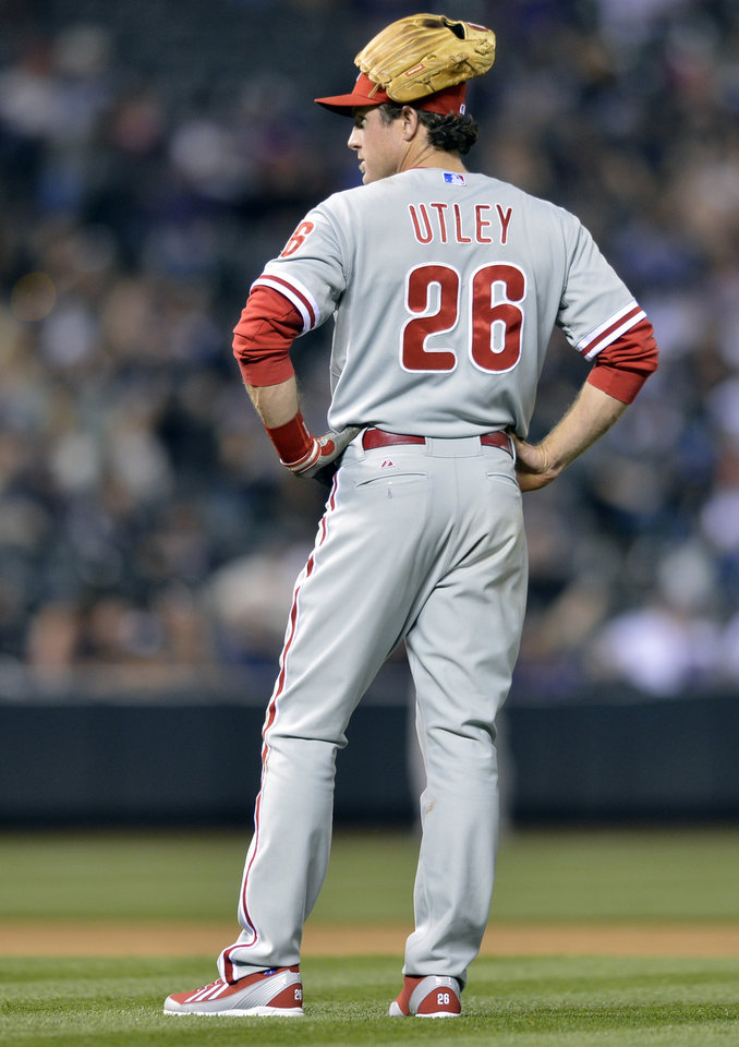 Photo - Philadelphia Phillies second baseman Chase Utley wears his glove on his head while waiting for a pitching change against the Colorado Rockies during the seventh inning of a baseball game on Friday, April 18, 2014, in Denver. (AP Photo/Jack Dempsey)