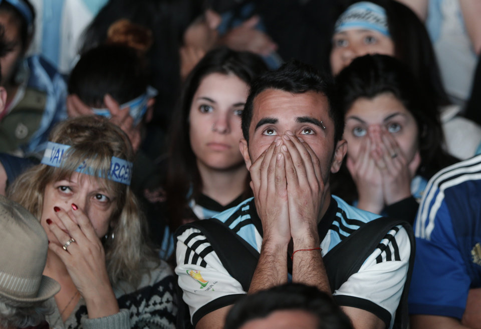 Photo - Argentina soccer fans watch in disbelief the final World Cup match between Argentina and Germany on an outdoor television screen set up in Buenos Aires, Argentina, Sunday, July 13, 2014. Mario Goetze volleyed in the winning goal in extra time to give Germany its fourth World Cup title with a 1-0 victory over Argentina. (AP Photo/Jorge Saenz)