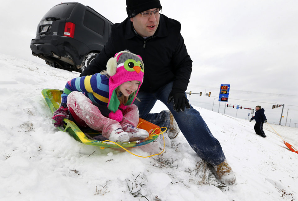 Joseph Haney helps daughter Sarah, 5, down the slope as they enjoy a snow holiday at Tecumseh Road and Interstate 35 on Friday, Dec. 6, 2013 in Norman, Okla.  Photo by Steve Sisney, The Oklahoman
