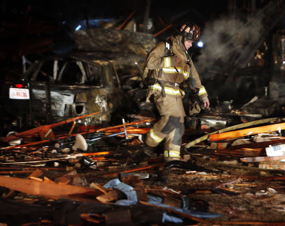 Photo - Firefighters walk look for hot spots in the remains of a house destroyed by a natural gas explosion.