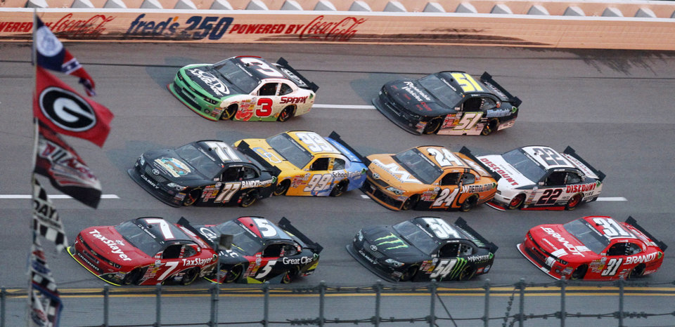 Photo - Regan Smith (7) leads a group of cars during the NASCAR Nationwide Series auto race at Talladega Superspeedway in Talladega, Ala., Saturday, May 4, 2013. Smith won the race. (AP Photo/Butch Dill)