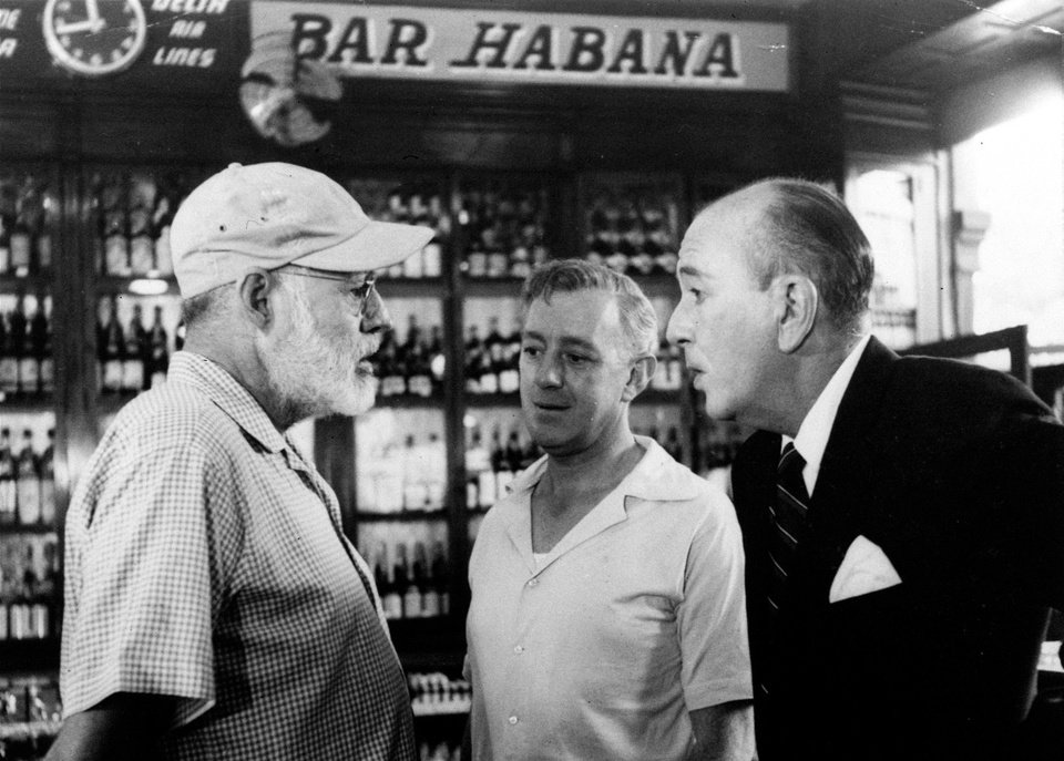 FILE - In this May 12, 1959, American novelist Ernest Hemingway, left, speaks with actors Alec Guinness, center, and Noel Coward in Sloppy Joe\'s Bar during the making of Sir Carol Reed\'s film version of