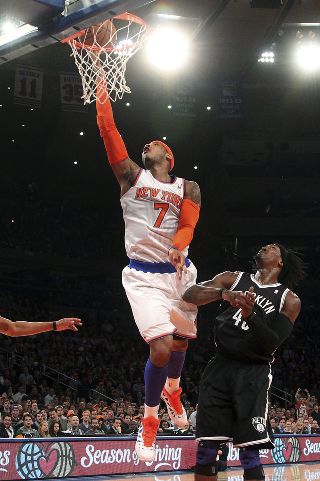 Photo - New York Knicks' Carmelo Anthony (7) shoots against Brooklyn Nets' Gerald Wallace during the first half of an NBA basketball game, Wednesday, Dec. 19, 2012, at Madison Square Garden in New York. (AP Photo/Mary Altaffer)