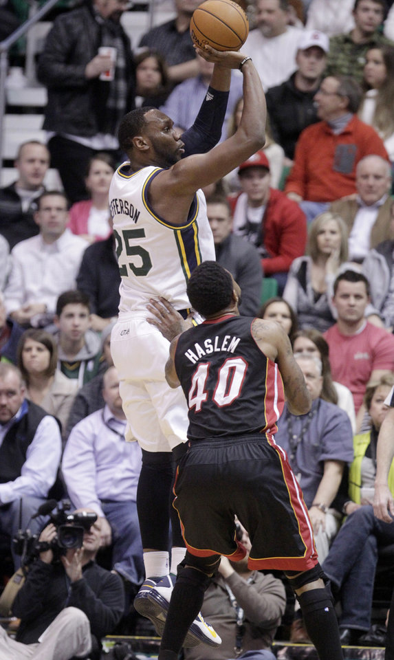 Photo - Utah Jazz center Al Jefferson (25) shoots as Miami Heat forward Udonis Haslem (40) looks on in the first quarter during an NBA basketball game Monday, Jan. 14, 2013, in Salt Lake City.  (AP Photo/Rick Bowmer)