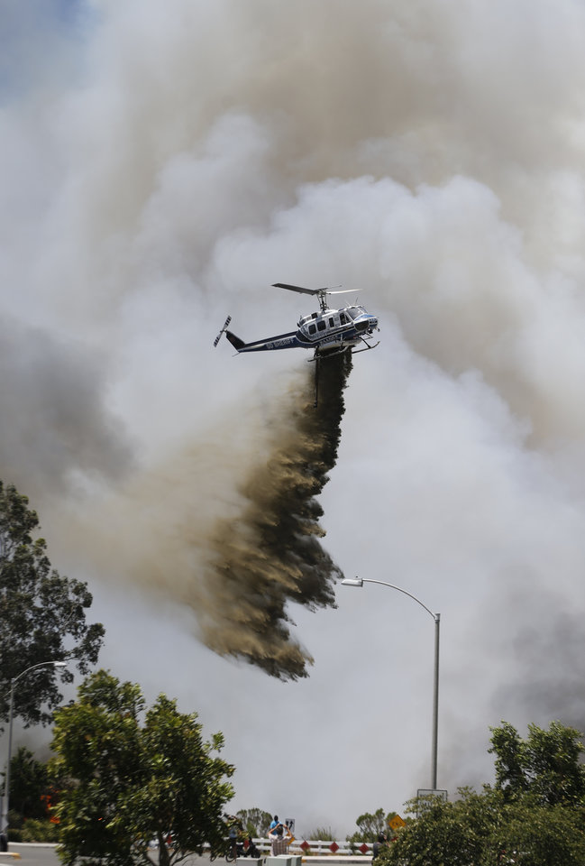 Photo - A helicopter drops a fire retardant on a wild fire Wednesday, May 14, 2014, in Carlsbad, Calif. Wind-driven flames are threatening homes in the coastal city of Carlsbad, where officials have sent mandatory evacuation notices to more than 11,000 homes and businesses. (AP Photo)