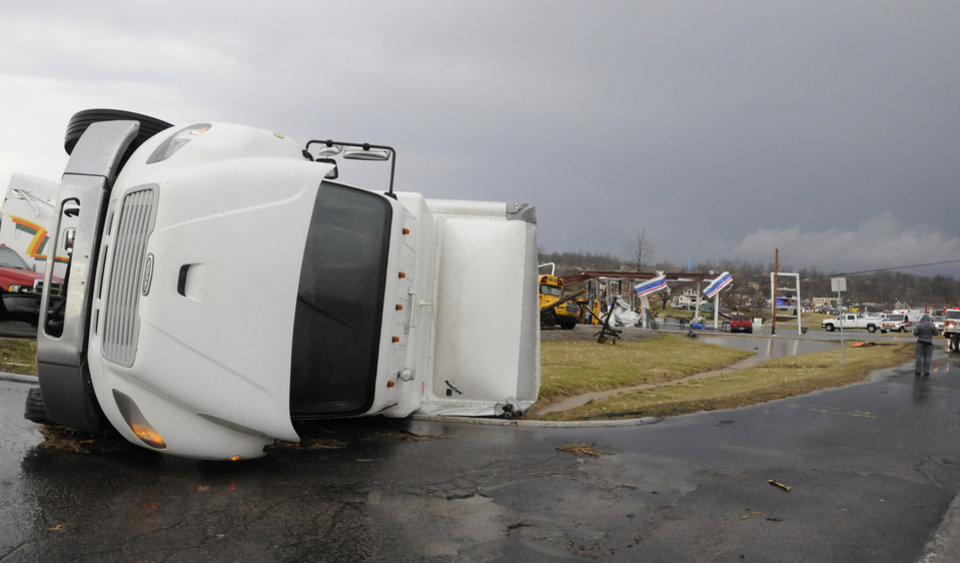 Photo -   A semitrailer lies on its side in front of the remains of a gas station following severe storms Friday, March 2, 2012, in Henryville, Ind. Tornadoes ripped across several small southern Indiana towns on Friday, killing at least three people and leaving behind miles of flattened devastation along the border with Kentucky. (AP Photo/Timothy D. Easley)