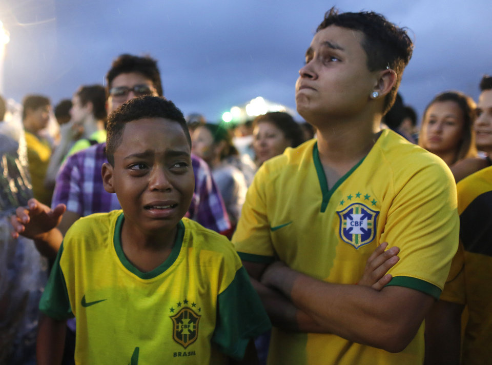 Photo - Brazil soccer fans cry as they watch their team get beat during a live telecast of the semi-finals World Cup soccer match between Brazil and Germany, inside the FIFA Fan Fest area on Copacabana beach in Rio de Janeiro, Brazil, Tuesday, July 08, 2014. (AP Photo/Leo Correa)