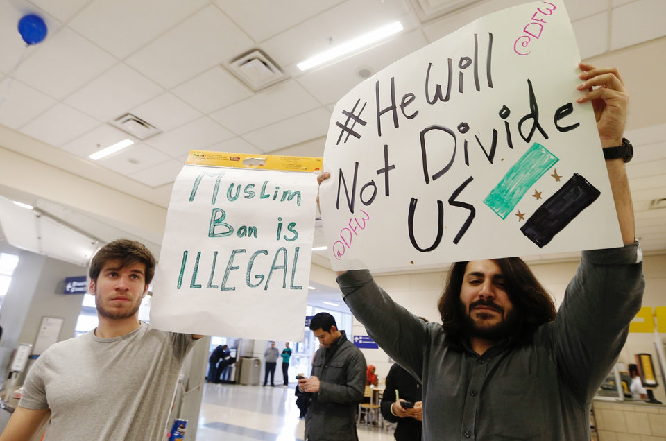 Photo - Southern Methodist University student Osama Aloabi, left, and his brother, a SMU graduate, Tarek Alolabi, right, demonstrate against President Donald Trump's executive order barring Muslims from certain middle eastern countries from entering the United States at Dallas Fort Worth Airport, Saturday, Jan. 28, 2017, in Dallas. The Aloabi's parents, who are Syrian, are being detained by immigration officials at the airport.  (Brandon Wade/Star-Telegram via AP)