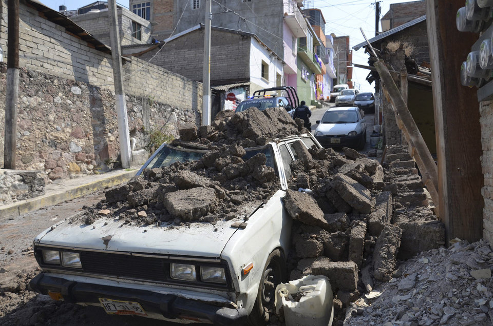 Photo - A parked car suffered damage when a adobe wall collapsed on it after a strong earthquake shook Chilpancingo, Mexico, Friday morning, April 18, 2014. A powerful magnitude-7.2 earthquake shook central and southern Mexico but there were no early reports of major damage or casualties. (AP Photo/Alejandrino Gonzalez)