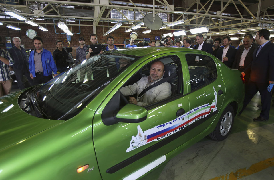 Photo - Iranian lawmaker Hossein Garousi drives a sedan called Runna, manufactured by the state-run Iran-Khodro automobile company in a ceremony marking the first shipment of automobiles to Russia since 2009, at company's plant near Tehran, Iran, Sunday, June 29, 2014. Iran began exporting automobiles to Russia for the first time in five years on Sunday, after meeting upgraded emission standards, the country's largest auto manufacturer said. (AP Photo/Vahid Salemi)
