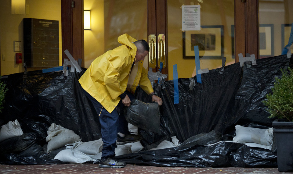Jose Alvarenga piles sandbags at the main entrance of a condominium building in the Old Town section of Alexandria, Va., Monday, Oct. 29, 2012, as residents brace for Hurricane Sandy.  (AP Photo/Manuel Balce Ceneta) ORG XMIT: VAMC101