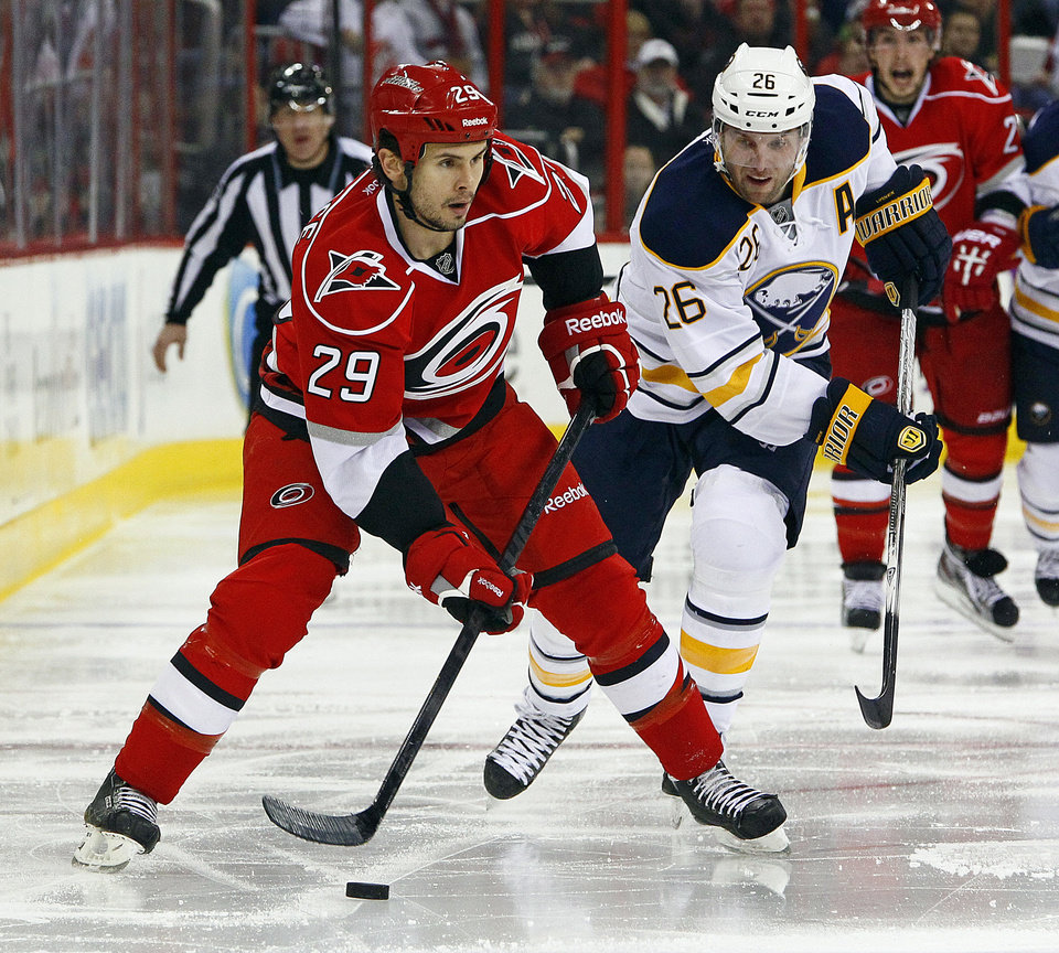 Carolina Hurricanes\' Tim Wallace (29) works the puck with Buffalo Sabres\' Thomas Vanek (26), of Austria, nearby during the second period of an NHL hockey game, Tuesday, March 5, 2013, in Raleigh, N.C. (AP Photo/Karl B DeBlaker)