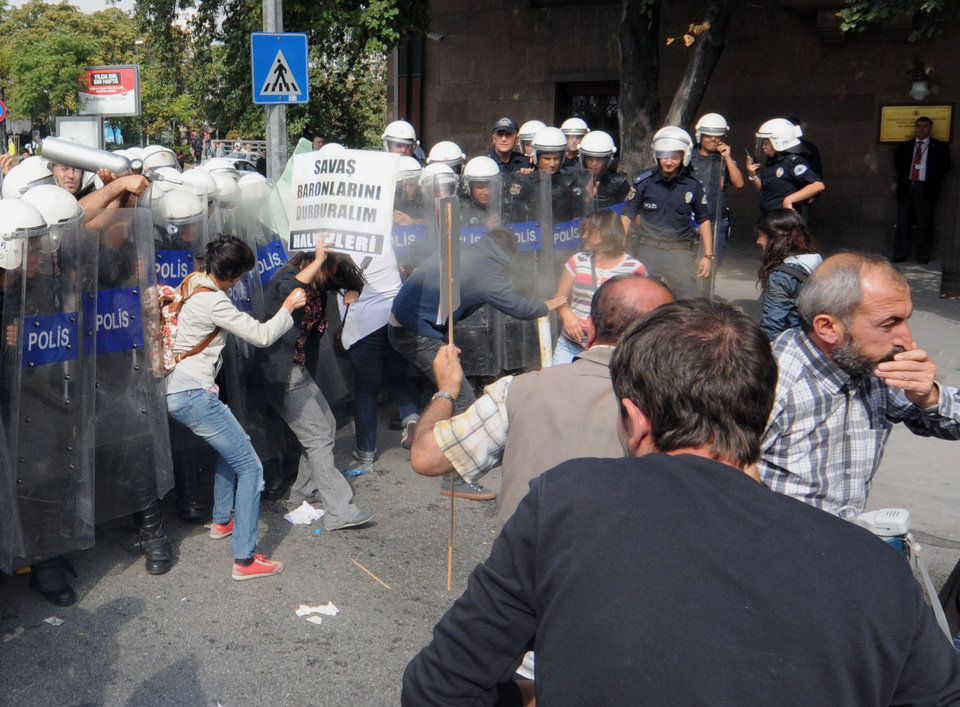 Riot police use pepper gas against the Turks protesting against a possible war with Syria during a debate at Turkey's parliament in Ankara, Turkey, Thursday, Oct. 4, 2012. Turkey fired on Syrian targets for a second day Thursday, but said it has no intention of declaring war, despite tensions after deadly shelling from Syria killed five civilians in a Turkish border town.Turkey's Parliament, meanwhile, began an emergency session to discuss a bill authorizing the military to launch cross border operations in Syria. If approved, the bill could more easily open the way to unilateral action by Turkey's armed forces inside Syria, without the involvement of its Western and Arab allies.(AP Photo)