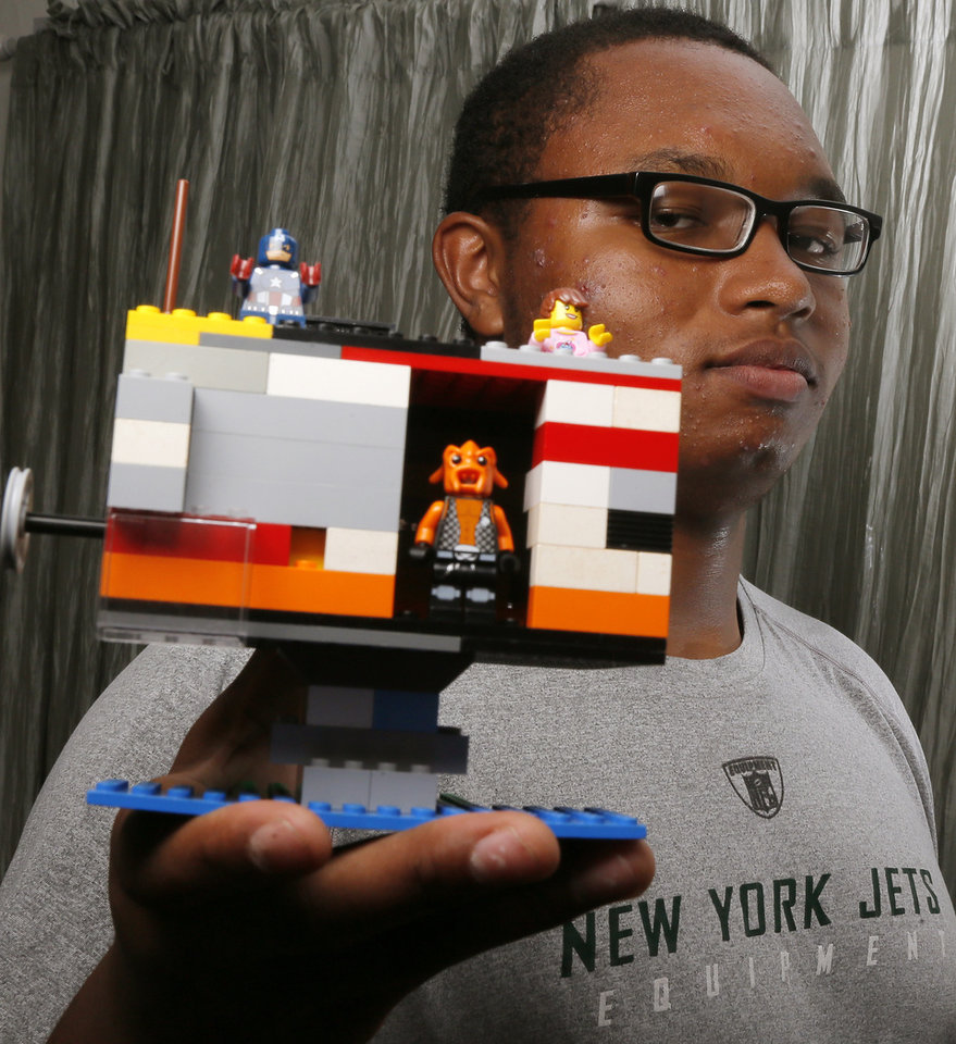 Photo - Douglass High School football player Mildren Montgomery shows a house he created from Lego blocks at his home in Oklahoma City, Wednesday, Oct. 30, 2013. The Douglass offense lineman committed to Texas Tech uses Lego blocks for his creative design outlet. Photo by Nate Billings, The Oklahoman