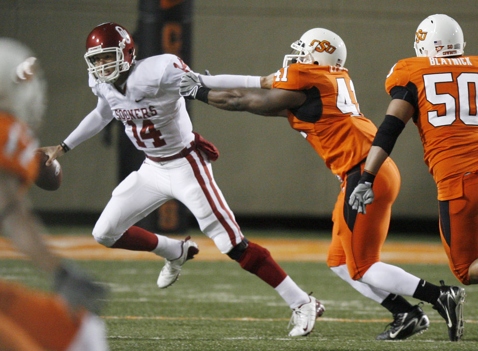 OU quarterback Sam Bradford tries to escape OSU's Orie Lemon during the first half of the college football game between the University of Oklahoma Sooners (OU) and Oklahoma State University Cowboys (OSU) at Boone Pickens Stadium on Saturday, Nov. 29, 2008, in Stillwater, Okla. STAFF PHOTO BY SARAH PHIPPS