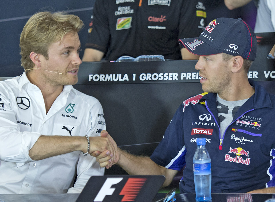 Photo - World Championship leader and Mercedes Formula One driver Nico Rosberg of Germany, left, shakes hands with Red Bull Formula One driver Sebastian Vettel of Germany, right, during a press conference in Hockenheim, Germany, Thursday, July 17, 2014. The German Grand Prix will be held on Sunday, July 20, 2014. (AP Photo/Jens Meyer)
