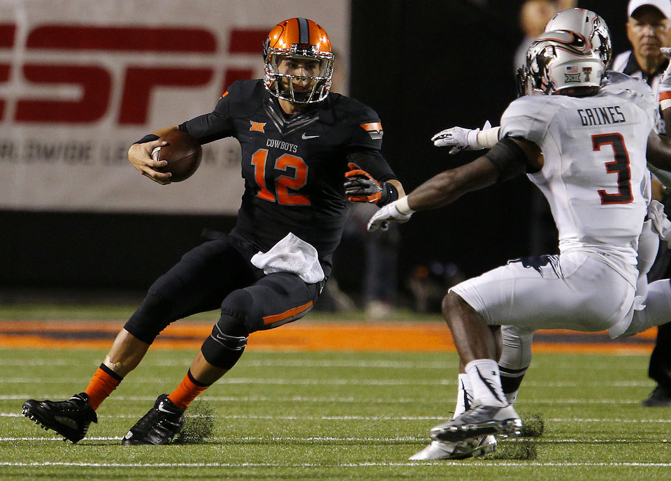 Photo - Oklahoma State's Daxx Garman (12) tries to get past Texas Tech's J.J. Gaines (3) during a college football game between the Oklahoma State Cowboys (OSU) and the Texas Tech Red Raiders at Boone Pickens Stadium in Stillwater, Okla., Thursday, Sept. 25, 2014. Photo by Bryan Terry, The Oklahoman