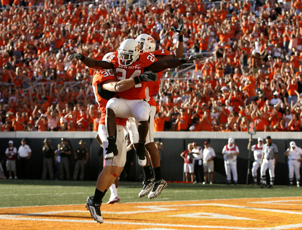 OSU\'s David Paulsen (30), Kendall Hunter (24) and Michael Harrison (7) celebrate a touchdown during the college football game between the Washington State Cougars (WSU) and the Oklahoma State Cowboys (OSU) at Boone Pickens Stadium in Stillwater, Okla., Saturday, September 4, 2010. Photo by Sarah Phipps, The Oklahoman