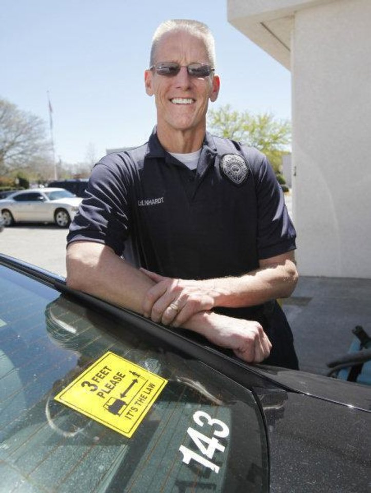 Edmond police Lt. Chuck Linhardt stands by a bumper sticker reminding drivers to stay three feet away from bicylists. PHOTO BYPAUL HELLSTERN, THE OKLAHOMAN PAUL HELLSTERN - THE OKLAHOMAN