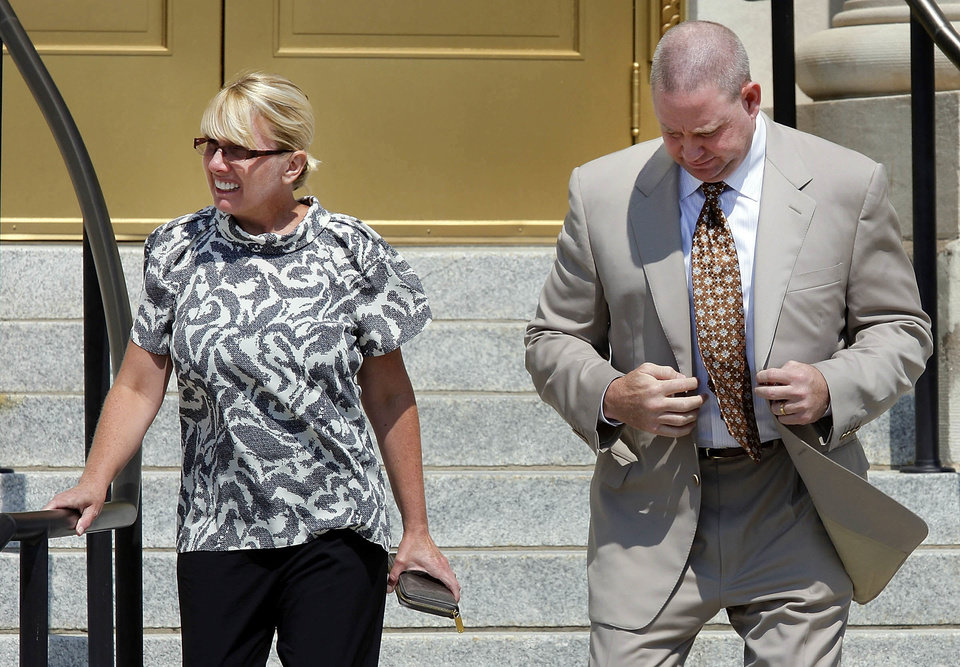 Photo - Lauri Ann Parsons, left, and her husband, Brent Alan Parsons, leave the U.S. Federal Courthouse in Muskogee, OK, on Monday, Aug. 5, 2013, after Lauri Parsons pleaded guilty to charges against her that were unsealed earlier in the morning. Brent was to have his hearing on the same charges later in the day.  Photo by Michael Wyke, Tulsa World  Michael Wyke - AP