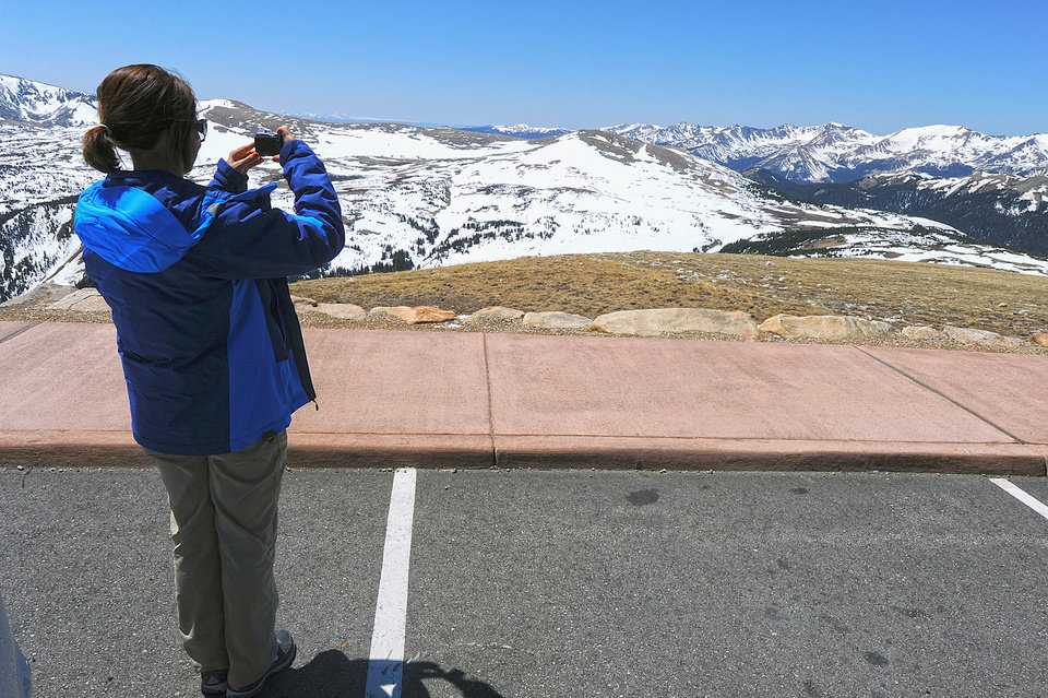 Photo - File - In this May 14 2012 file photo, Brazilian national Maria Mackmillan snaps a photo from Gore Overlook on Trail Ridge Road, in Rocky Mountain National Park outside Estes Park, Colo. Two fatal lightning strikes on consecutive days in July 2014 pinpoint dangers not always apparent to visitors to the 11,000-foot exposed high country of Rocky Mountain National Park. Afternoon storms visible miles away arrive overhead suddenly. (AP Photo/The Daily Camera, Walt Hester, file)
