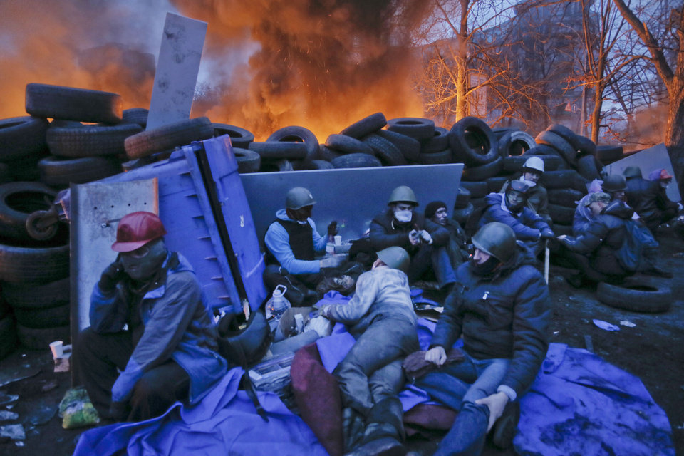 Photo - Activists have a rest at the burning barricades, on the side of bloody clashes close to Independence Square, the epicenter of the country's current unrest, Kiev, Ukraine, Thursday, Feb. 20, 2014. Fearing that a call for a truce was a ruse, protesters tossed firebombs and advanced upon police lines Thursday in Ukraine's embattled capital. Government snipers shot back and the almost medieval melee that ensued left scores of people dead. (AP Photo/Efrem Lukatsky)