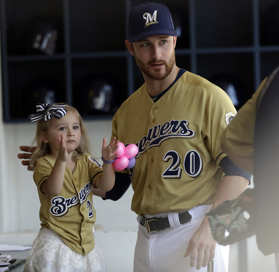 Milwaukee Brewers catcher Jonathan Lucroy shows his daughter Ellia around the dugout before a baseball game against the Miami Marlins, Sunday, July 21, 2013, in Milwaukee. (AP Photo/Morry Gash)