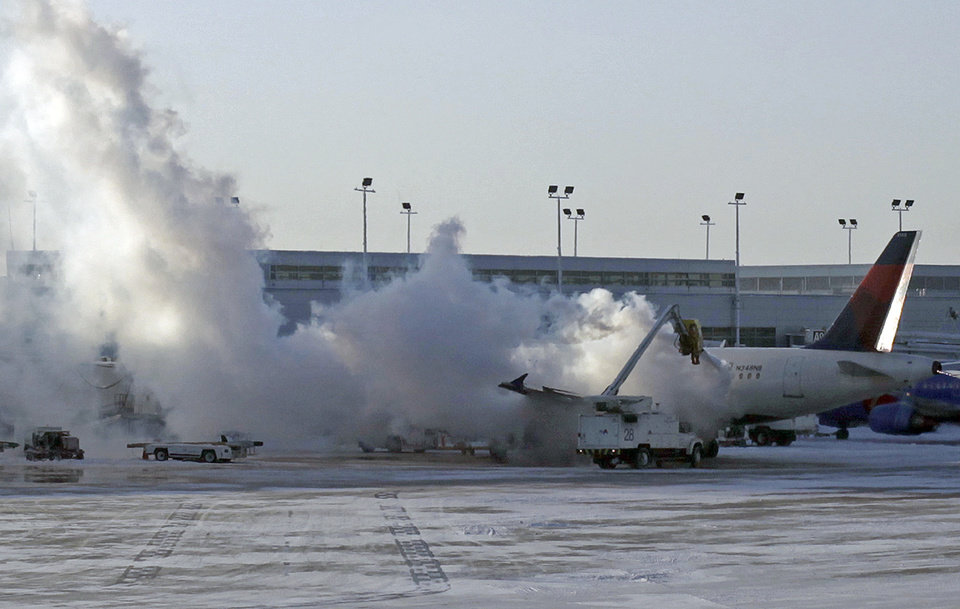 Photo - A Delta plane is deiced at Chicago Midway International Airport Monday, Jan. 6, 2014, in Chicago. The bitter weather comes after a heavy snowstorm hit much of the region last week.   More than 400 flights were cancelled at Chicago's airports Monday.(AP Photo/Kiichiro Sato)