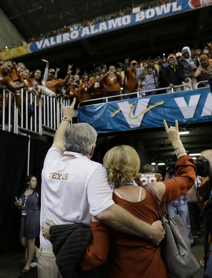Photo - Texas coach Mack Brown, left, and his wife Sally, right, wave to fans as they depart after  the Valero Alamo Bowl NCAA college football game against Oregon, Monday,  Dec. 30, 2013, in San Antonio. Oregon won 30-7. (AP Photo/Eric Gay)