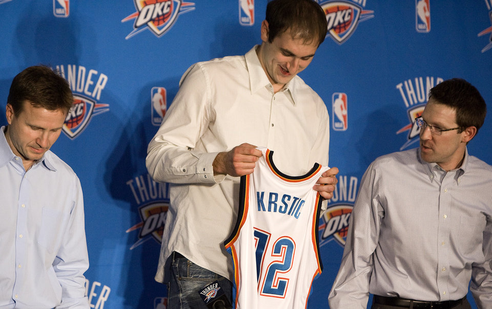 Photo -  NBA BASKETBALL: New center Nenad Krstic looks at his  Oklahoma City Thunder jersey as Thunder executive vice president and general manager Sam Presti and head coach Scott Brooks look on ,Tuesday, Dec. 30, 2008, at the Thunder practice facility in Oklahoma City. PHOTO BY SARAH PHIPPS, THE OKLAHOMAN ORG XMIT: KOD