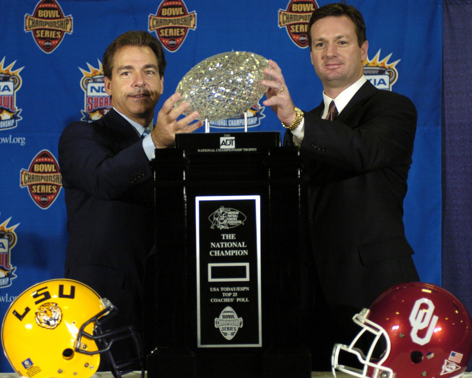 Photo - COLLEGE FOOTBALL: Louisiana State University coach Nick Saban and University of OKlahoma coach Bob Stoops pose for photographers in front of the ADT National Championship trophy during a news conference in New Orleans, Saturday,  January 3, 2004.  The LSU football team will face OU in the Sugar Bowl Sunday.  Staff photo by Bryan Terry