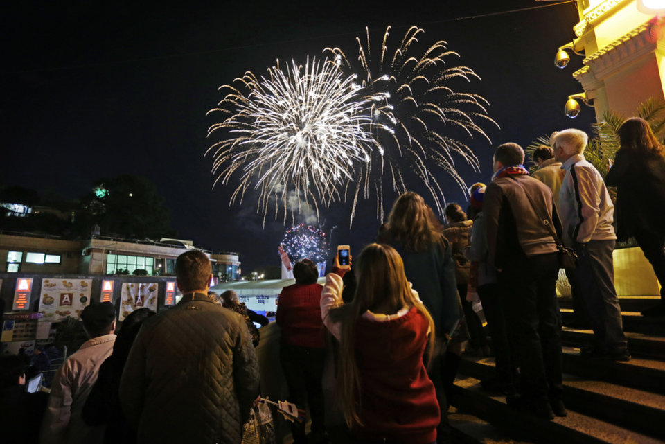 Photo - Fireworks go off over the Black Sea as the public gathers at a 2014 Winter Olympics Live Site which broadcasts televised coverage on giant monitors, Saturday, Feb. 15, 2014, in central Sochi, Russia. (AP Photo/David Goldman)