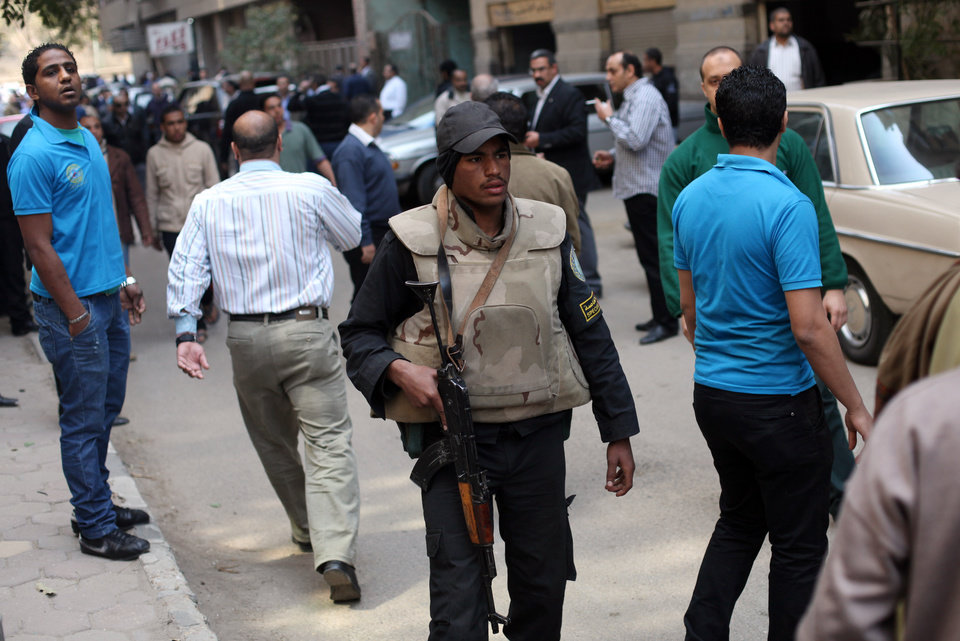 An Egyptian policeman holds a gun, as police officers arrest Ahmed Qaddaf al-Dam, cousin of Libya�s former dictator Moammar Gadhafi, not pictured, in Cairo, Egypt, March 19. 2013.  Egyptian security forces arrested a cousin of Libya�s former dictator Moammar Gadhafi on Tuesday following an hours-long siege of his home in central Cairo, a security official and witnesses said. (AP Photo/Khalil Hamra)