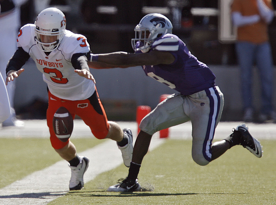 Photo - Oklahoma State's Brandon Weeden (3) fumbles the ball out of bounds as he is hit by Kansas State's Stephen Harrison (8) during the second half of the college football game between the Oklahoma State University Cowboys (OSU) and the Kansas State University Wildcats (KSU) on Saturday, Oct. 30, 2010, in Manhattan, Kan.   Photo by Chris Landsberger, The Oklahoman