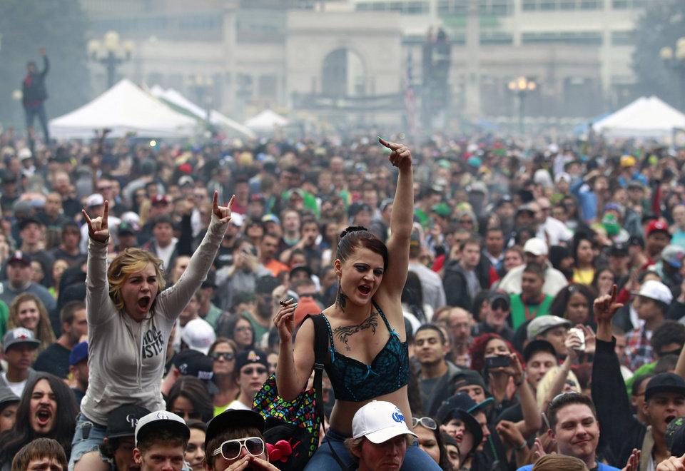 FILE - In this April 20, 2013 file photo, members of a crowd numbering tens of thousands smoke marijuana and listen to live music, at the Denver 420 pro-marijuana rally at Civic Center Park in Denver. The U.S. government said Thursday, Aug. 29, 2013 that the federal government will not make it a priority to block marijuana legalization in Colorado or Washington or close down recreational marijuana stores, so long as the stores abide by state regulations. (AP Photo/Brennan Linsley, File)
