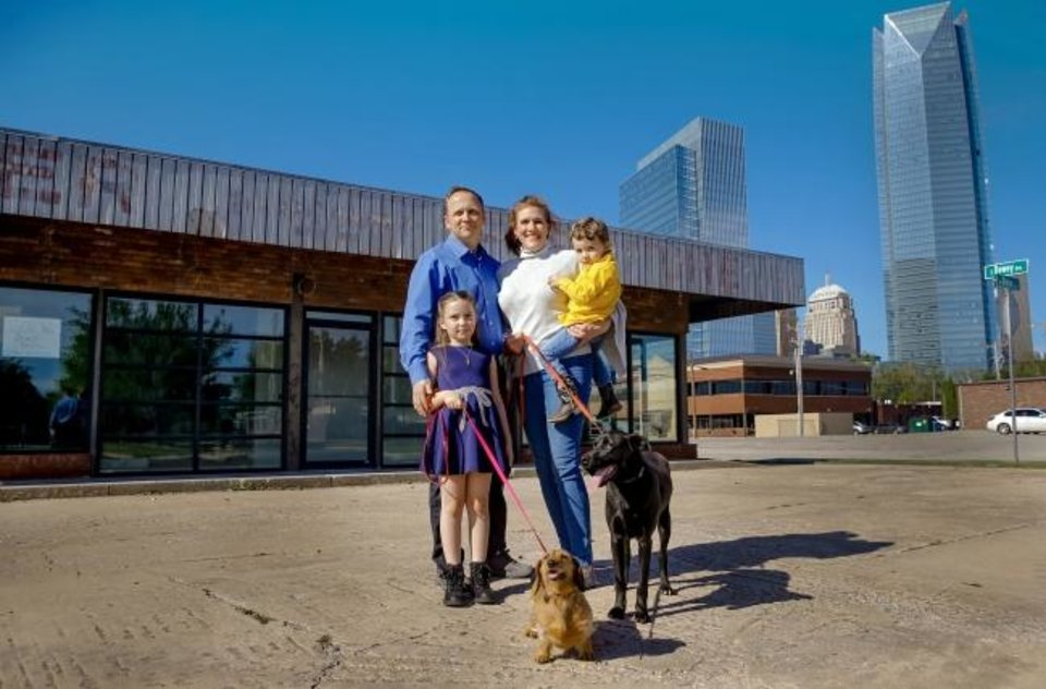 Photo -  Tristan Young, left, and Shara Carlton enjoy a moment with their children Kadence and J.D. Young and dogs Fawn, center, and Alex at their new OKC Vet Campus opening next month 601 W Reno Ave. [Chris Landsberger/The Oklahoman]